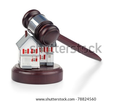 Closeup of a toy house model and a brown gavel against a white background - stock photo