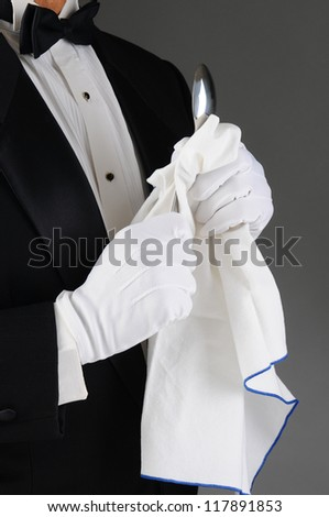 Closeup of a waiter wearing a tuxedo polishing a spoon. Vertical format on a light to dark gray background. Man is unrecognizable. - stock photo