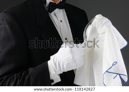 Closeup of a waiter wearing a tuxedo polishing a wineglass. Horizontal format on a light to dark gray background. Man is unrecognizable. - stock photo