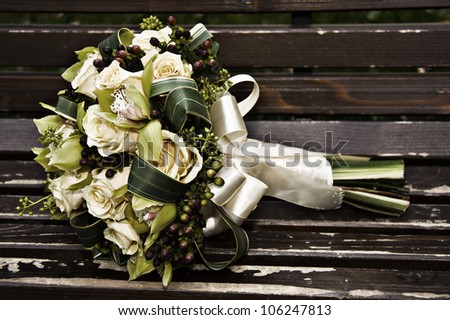 Closeup of a wedding bouquet on a bench outdoors - stock photo