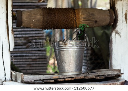 Closeup of a well with pulley and aluminum bucket - stock photo
