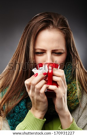 Closeup of a woman feeling sick with a cold, wrapped up in a woolly scarf and drinking hot tea over gray background - stock photo