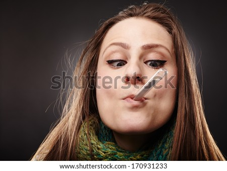 Closeup of a woman making a funny face while holding a thermometer in her mouth over gray background - stock photo