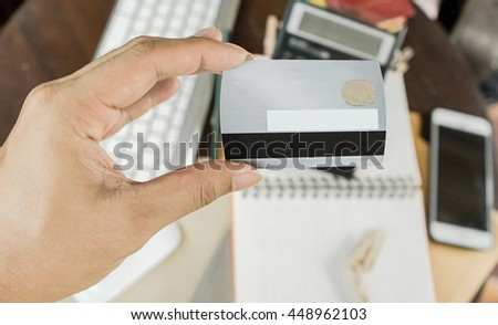 Closeup of a woman's hand holding up a credit card, selective focus on hand, can be used for e-commerce, business and technology concept, Vintage tone - stock photo