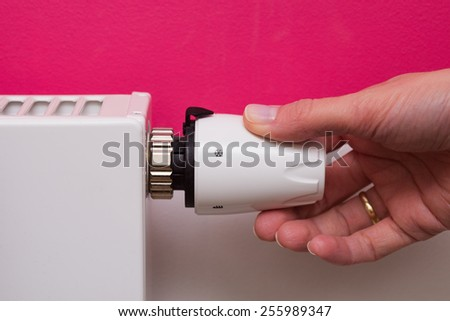 Closeup of a woman's hand setting the room temperature By Thermostat. Radiator adjustment to save energy. Save energy and money concept - stock photo