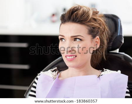 Closeup of a worried woman patient waiting to be checked up at the dentist - stock photo