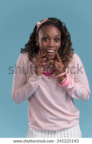 Closeup of a young African woman looking surprised on blue background - stock photo