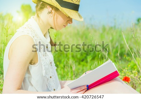Closeup of a young and caucasian woman sitting in a park,reading a book - lifestyle,people and outdoor  - stock photo