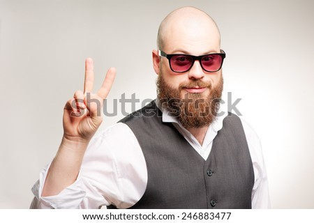 closeup of a young bearded caucasian man with sunglasses showing victory sign on grey background - stock photo