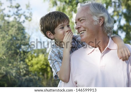 Closeup of a young boy whispering in grandfather's ear outdoors - stock photo