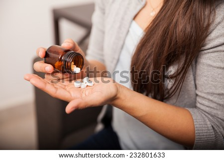 Closeup of a young brunette getting some aspirins from a bottle at home - stock photo