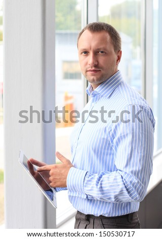 Closeup of a young business man at his office and using his modern tablet pc to do his work  - stock photo