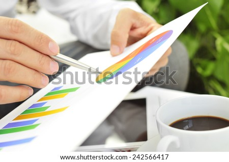 closeup of a young businessman checking some charts - stock photo