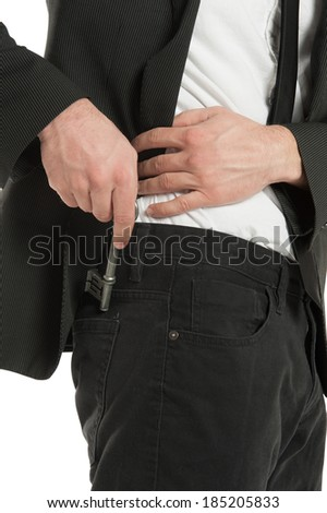 Closeup of a young businessman places a skeleton key in his back pocket, isolated on white background - stock photo