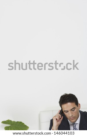 Closeup of a young businessman using mobile phone in white office - stock photo