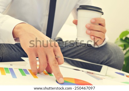 closeup of a young businessman with a cup of coffee in his hand checks some charts - stock photo