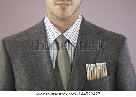Closeup of a young businessman with pencils in pocket against purple background - stock photo