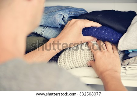 closeup of a young caucasian man arranging the closet - stock photo
