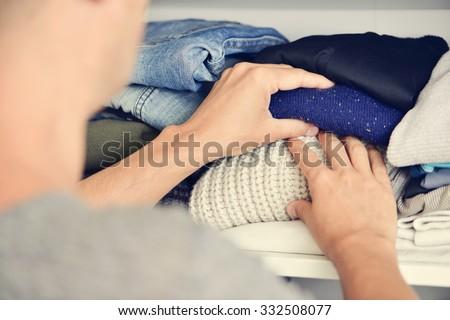 closeup of a young caucasian man arranging the closet - stock photo
