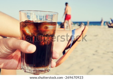closeup of a young caucasian man hanging out on the beach with a glass with cola drink - stock photo