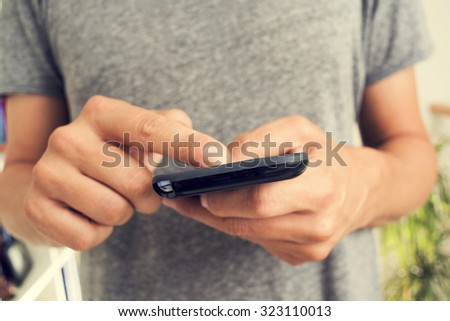 closeup of a young caucasian man in a gray t-shirt using a smartphone indoors - stock photo