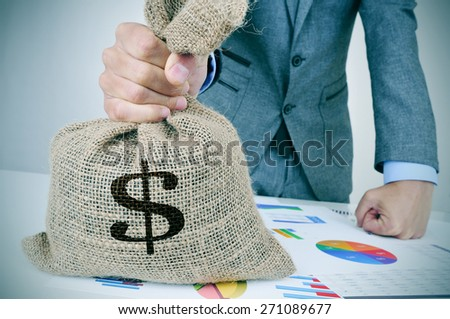 closeup of a young caucasian man in a grey suit with a money bag on a desk full of different charts - stock photo