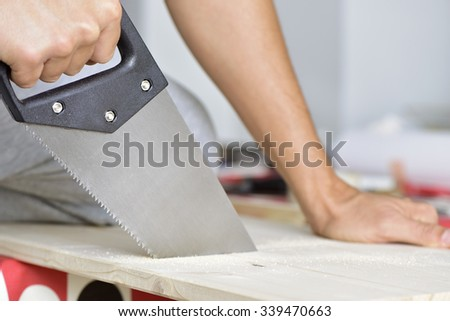 closeup of a young caucasian man sawing a wooden board with a handsaw - stock photo