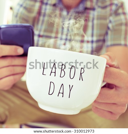 closeup of a young caucasian man with a smartphone and a mug with the text labor day - stock photo