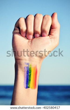 closeup of a young caucasian man with his fist raised to the sky and a rainbow flag painted in his wrist, with the ocean in the background - stock photo