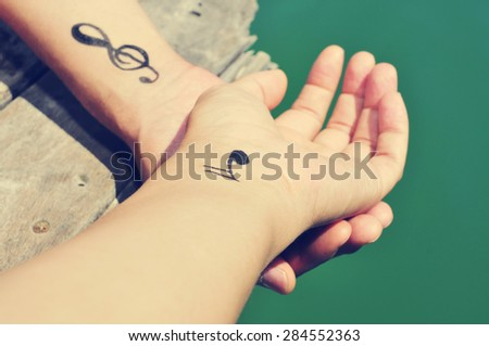 closeup of a young caucasian man with some musical symbols tattooed in his wrists, chilling out on a wooden pier at the sea - stock photo