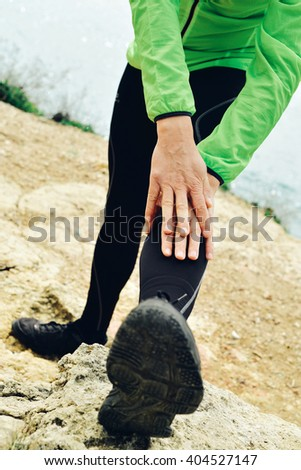 closeup of a young caucasian sportsman wearing sport clothes stretching his legs before or after running - stock photo