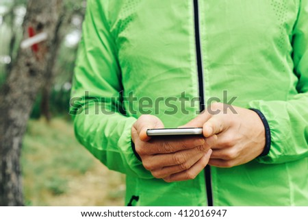 closeup of a young caucasian sportsman wearing sport clothes using his smartphone outdoors - stock photo