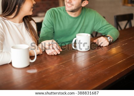 Closeup of a young couple holding hands and drinking coffee during a date in a cafe - stock photo