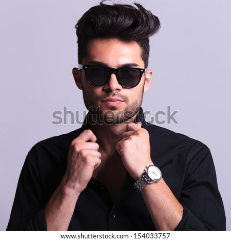 closeup of a young fashion man holding his hands on the collar of his shirt while looking at the camera. isolated on a gray background - stock photo