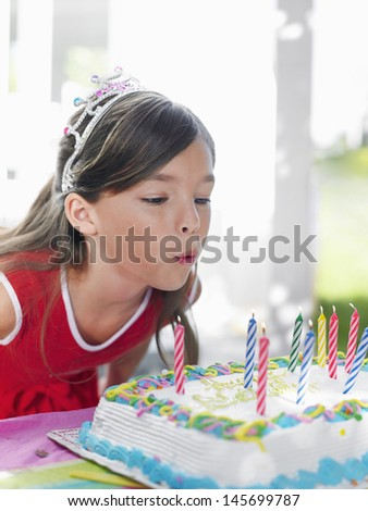 Closeup of a young girl blowing out birthday candles - stock photo