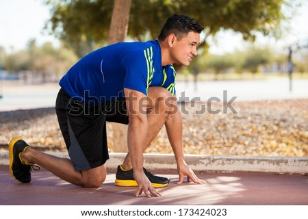 Closeup of a young Hispanic athlete in the ready position before going for a run - stock photo