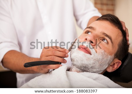 Closeup of a young man getting a close shave at a barber shop - stock photo