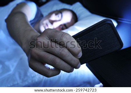 closeup of a young man in bed looking at the smartphone at night - stock photo