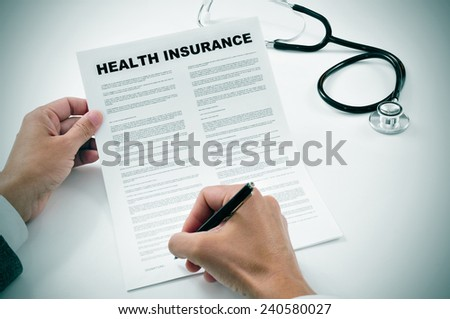 closeup of a young man signing a health insurance policy - stock photo