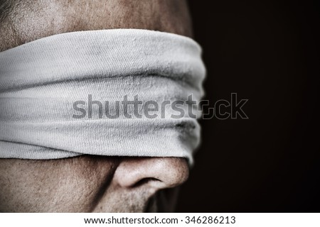 closeup of a young man with a blindfold in his eyes, as a symbol of oppression or repression, with a dramatic effect - stock photo