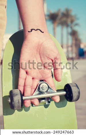 closeup of a young man with a moustache tattooed in his hand, holding a skateboard - stock photo