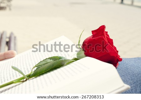closeup of a young man with a red rose on an open book for Sant Jordi, the Saint Georges Day, when it is tradition to give red roses and books in Catalonia, Spain - stock photo