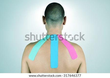 closeup of a young man with some strips of elastic therapeutic tape of different colors in his back - stock photo