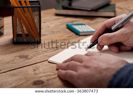 Closeup of a young man writes  in a notebook. Copy space - stock photo