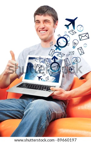 Closeup of a young smiling business man sitting at his home office and using his modern laptop to do his work - stock photo