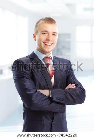 Closeup of a young smiling business man standing in his modern business office - stock photo