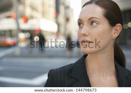 Closeup of a young thoughtful businesswoman looking away against the road - stock photo