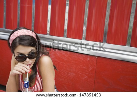 Closeup of a young woman in sunglasses drinking soda - stock photo