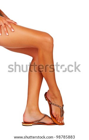 Closeup of a young woman tanned legs in summer fashion sandals on white studio background - stock photo