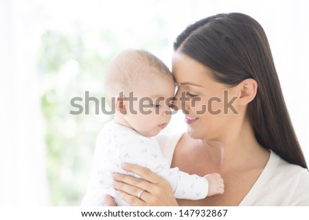 Closeup of a young woman with her cute little baby - stock photo